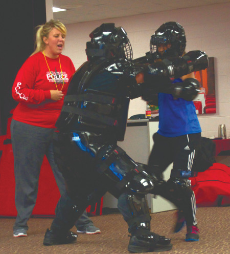 Officers Joy Paquette and James Wing instruct a female participant during the two-day Rape Aggression Defense class. Sgt. Wing and students dress in full protective gear as they practiced defense tactics.  Photo By: Melanie Ronquillo | Photographer